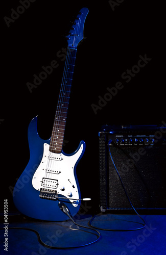 Poster electric guitar and combo amplifier in rays of blue light