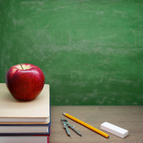 Back To School - A Red Apple on a Pile of Books in front of a Chalkboard
