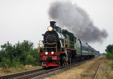 Old steam locomotive travels by rail