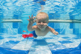 Smiling baby boy diving underwater with fun for red flower in blue pool Active lifestyle, child swimming lesson with parents, and water sports activity during family summer vacation in tropical resort