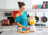 Fototapety Fit woman in workout gear in kitchen making a smoothie