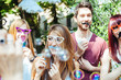 Obrazy na płótnie, fototapety, zdjęcia, fotoobrazy drukowane : Party! A group of friends, three women and a man have fun at a party in a park with a mustache and fake glasses, joking and talking to each other and playing with soap bubbles in the air!