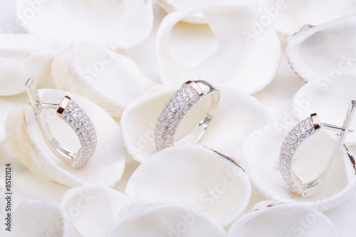 obraz PCV Beautiful gold ring and earrings with diamonds on white seashells.