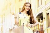Стильна красивая девушка в желтом платье на прогулке в городе