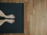 Feet on yoga mat, doing yoga at home