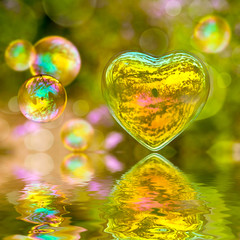 Soap bubble in the shape of a heart with reflections