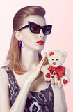 Portrait Fashion  girl in glasses, Loving teddy bear with red