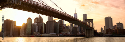 Manhattan skyline panorama and Brooklyn Bridge at sunset, New York