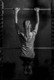 Athletic young woman showing muscles of the back and arms while training on black background - 85243118
