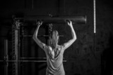 Athletic young woman showing muscles of the back and hands while training on black background - 85243172