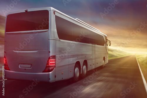 Fototapeta Coach driving into sunset
