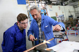 Teacher with student in metallurgy workshop poster