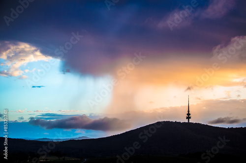 Rain clouds accumulated behind the Black Mountain in Canberra, Australia in the плакат
