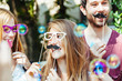 Obrazy na płótnie, fototapety, zdjęcia, fotoobrazy drukowane : Party! A group of friends, two women and a man have fun at a party in a park with a mustache and fake glasses, joking and talking to each other and playing with soap bubbles in the air!