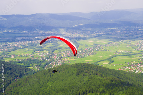 Fototapeta Paraglider over village in mountain