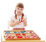 Fototapety Little girl running with the letters in Montessori kindergarten