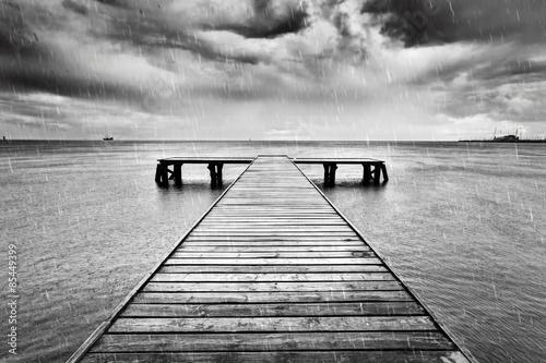 Stary molo, molo na morzu. Czarno-biały, deszcz.