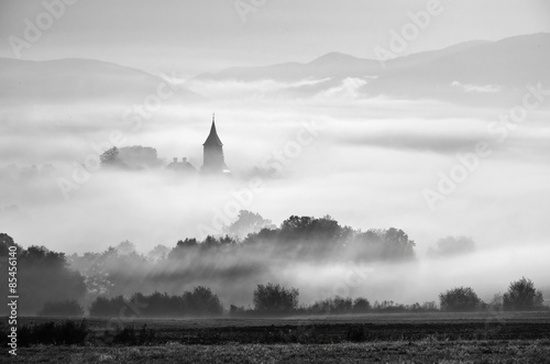 Tower of rural church in misty autumn morning. - 85456140