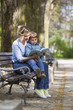 Obrazy na płótnie, fototapety, zdjęcia, fotoobrazy drukowane : Mother and son sitting on a bench in a park and reading a book