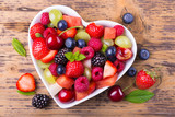 Fototapety Fruit salad in heart shaped bowl - healthy eating