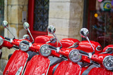 Red retro scooters parked on a Parisian street