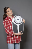 healthy 30s woman holding a weight scale, symbol of healthcare poster
