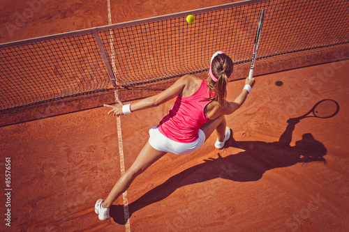 Poster Young woman playing tennis.High angle view.Forehand volley.