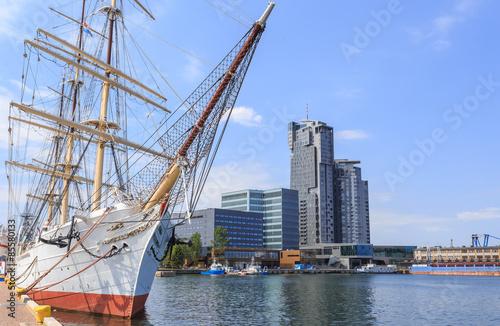 Zdjęcia na płótnie, fototapety na wymiar, obrazy na ścianę : Gdynia nad morzem Bałtyckim. Statek Żaglowy (3 - masztowa fregata) zacumowany przy Molo Południowym Portu w Gdyni. W głębi widać wieże drapacza chmur