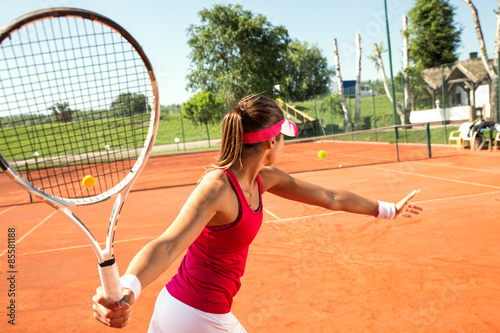Poster Young woman playing tennis.High angle view.Forehand.