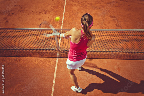 Young woman playing tennis.High angle view.Backhand volley. Tableau sur Toile