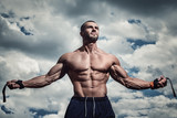 Fototapety Muscular man under cloudy sky
