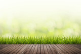 Fotoroleta grass with green blurred background and wood floor