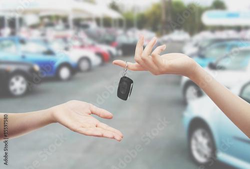Chiavi consegnate in mano sfondo parcheggio auto Poster