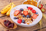 Healthy breakfast with fresh fruits, yogurt and granola on rustic wooden table