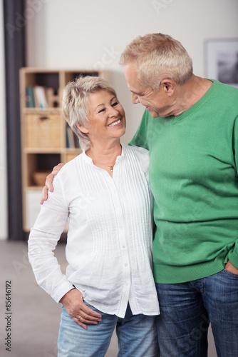 Poster lachendes älteres paar in ihrem wohnzimmer
