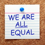 The phrase We Are All Equal in blue text on an index card pinned to a cork notice board as a reminder
