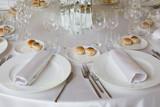 Tavolo apparecchiato con piatti e tovaglioli in primo piano