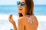Woman using sun cream on the beach - Fine Art prints