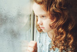 Fototapety Portrait of a sad child looking out the window. Toning photo.