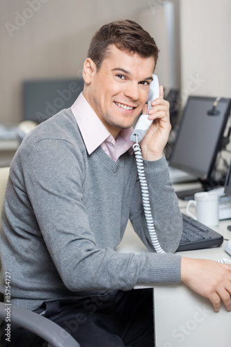 Male Customer Service Representative Using Telephone At Desk