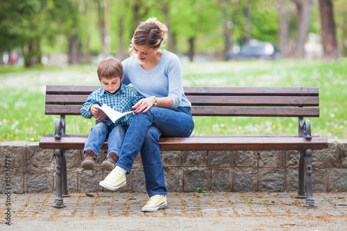 Zdjęcia na płótnie, fototapety, obrazy : Mother and son sitting on a bench in a park and reading a book