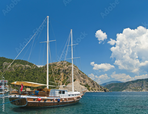 Aluminium tourist boat moored at bay surrounded by mountains