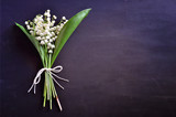 Bouquet of lily of the valley flowers on dark background, copy space
