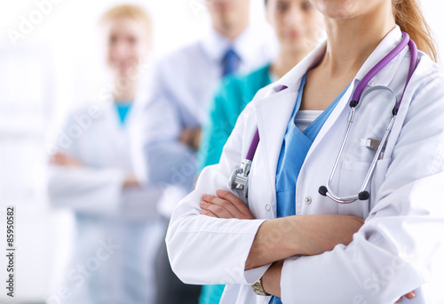 Attractive female doctor in front of medical group Plakat