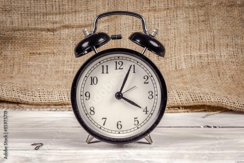 Naklejka Classic alarm clock on a wooden table