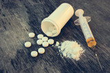 drug addiction on the old wooden background. White pill, syringe and heroin. Toned image.