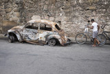 Fotoroleta Scene at the entrance to the Vidigal favela in Rio de Janeiro features an old burned out ruined fusca car