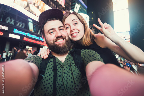 Happy dating couple in love taking selfie photo on Times Square in New York whil Poster