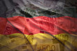 colorful waving german flag on a euro money background