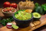 Fototapety A delicious Bowl of Guacamole next to fresh ingredients on a table with tortilla chips and salsa